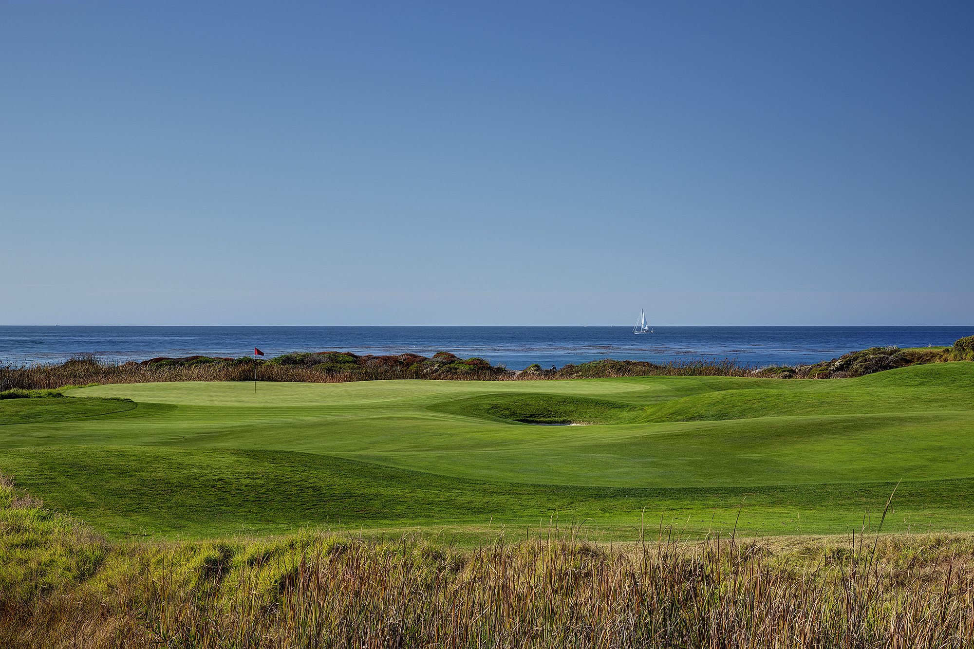 The 7th green at The Links of Spanish Bay with the Pacific Ocean and a sail boat in the background