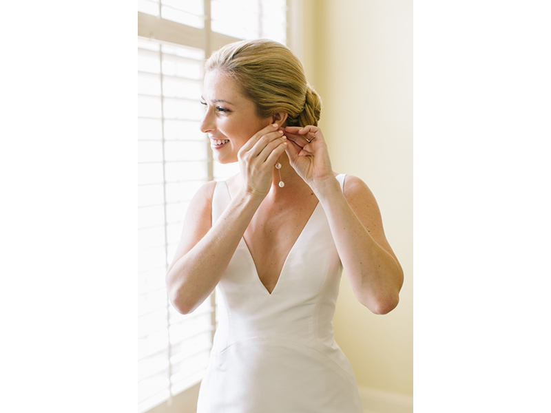 Bride putting in earring.