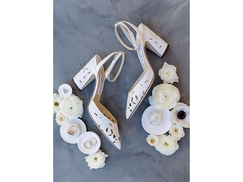 White Jimmy Choo heels displayed with white flowers and wedding rings in ring dishes
