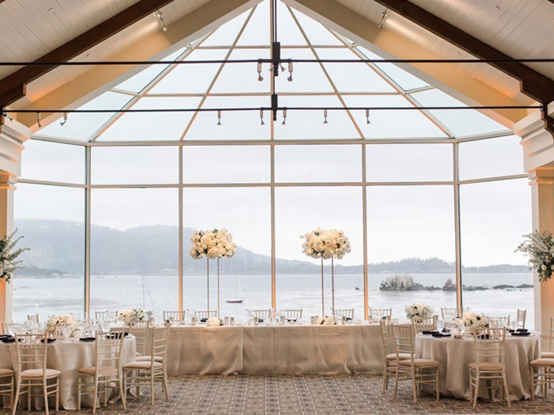 The Beach and Tennis Club dining room set for a wedding with long head table and tall flower arrangements