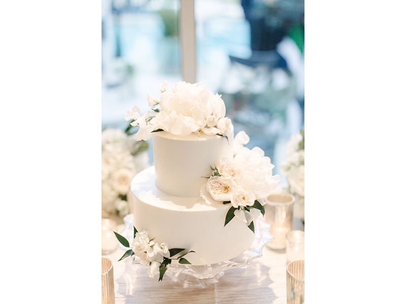 Two-tiered wedding cake with white flowers