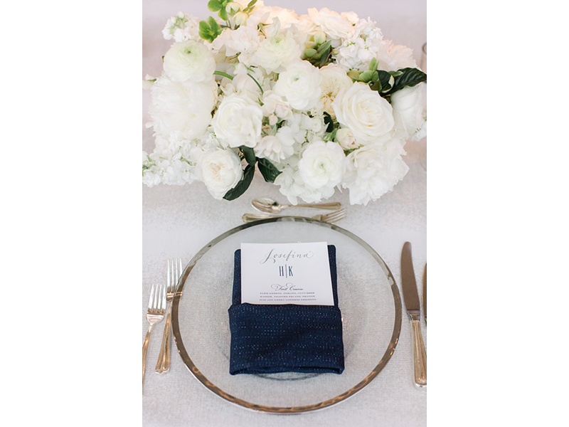 Wedding table setting with gold flatware navy blue linens and white flowers