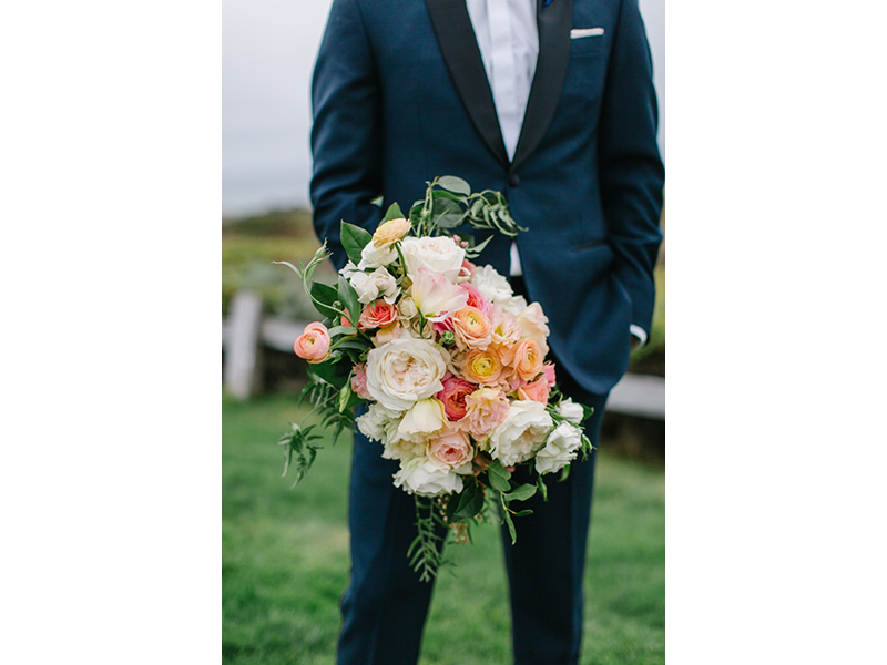 Groom holding bride's bouquet, garden roses in shades of pink with greenery.