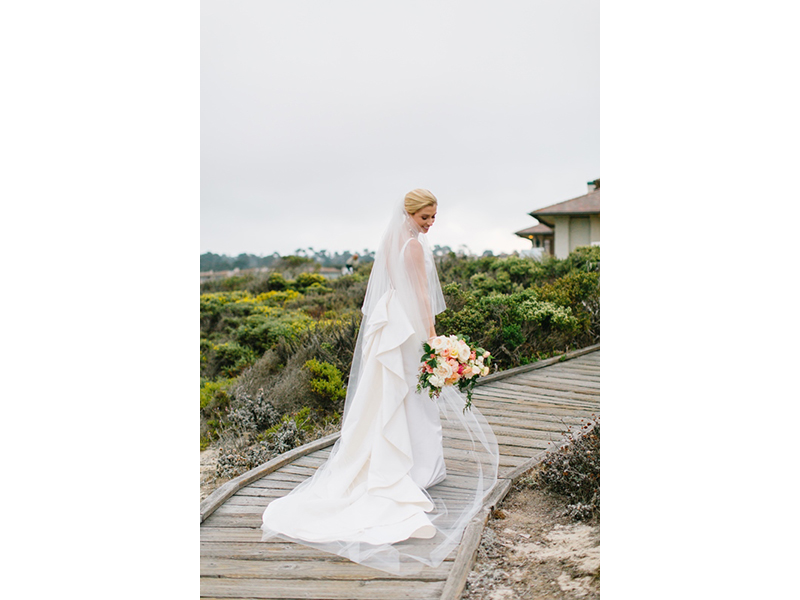 A bride at Spanish Bay with long veil and bouquet.