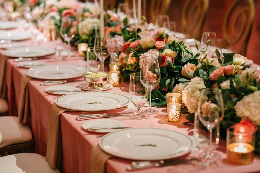 Wedding table setting with pink tablecloth and floral garland