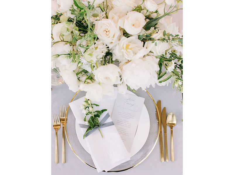 Wedding table setting with gold flatware and flowers