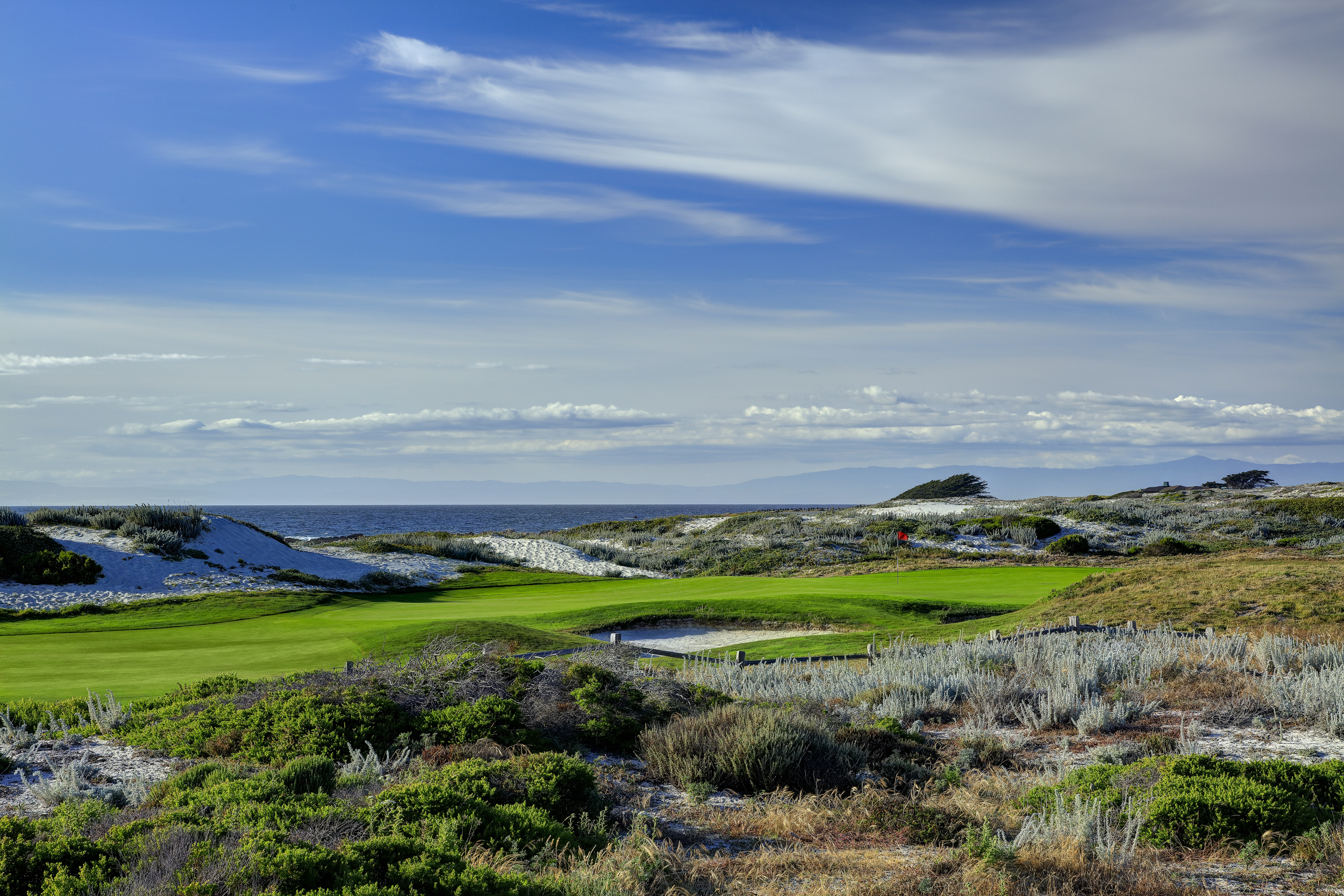 A green golf course surrounded with short shrubs and the ocean in the distance on a partly cloudy day.