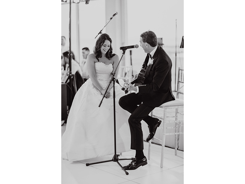Black and white photo with father of the bride playing guitar to smiling bride
