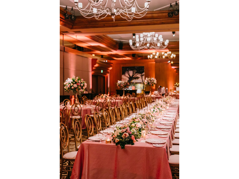 Spanish Bay ballroom set up for wedding reception with pink tablecloths and florals