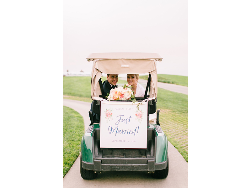 Bride and groom in golf cart with just married sign