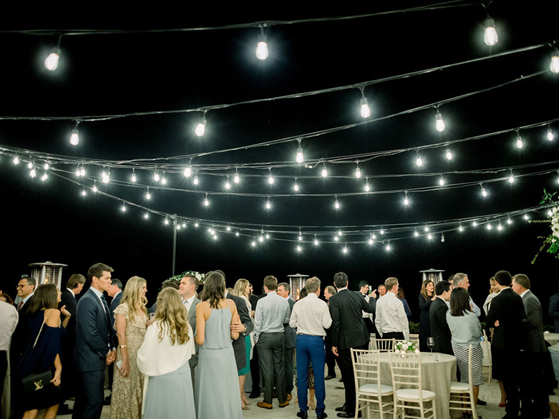 Beach & Tennis Club patio at night with market lights and wedding attendees