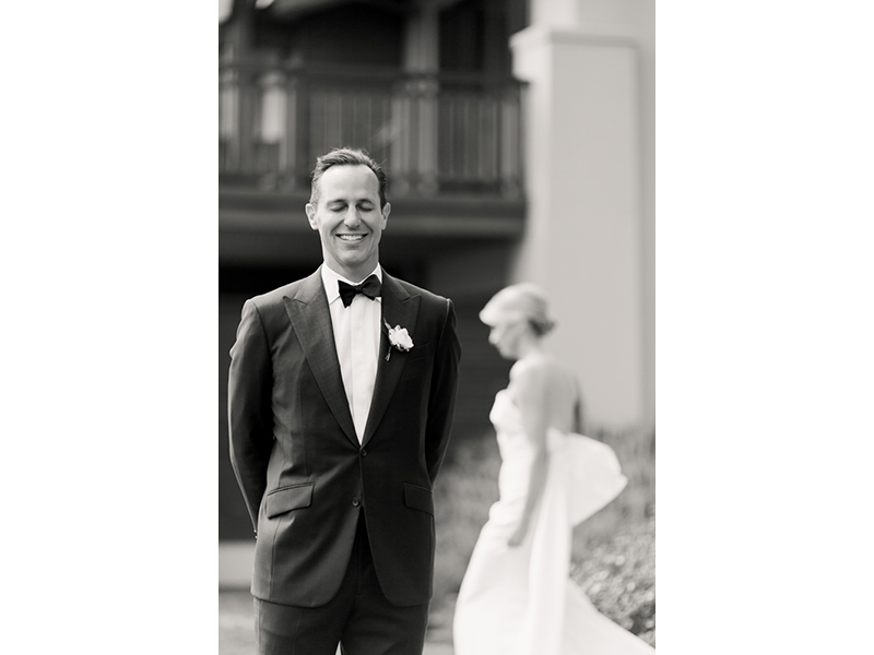 Black and white photo of groom in tux with bride in background