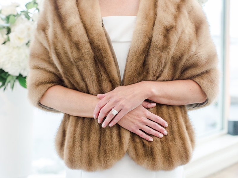 Close up of bride's torso and arms wearing fur stole