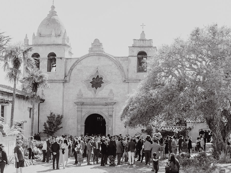 Black and white photo of church with wedding attendees outside