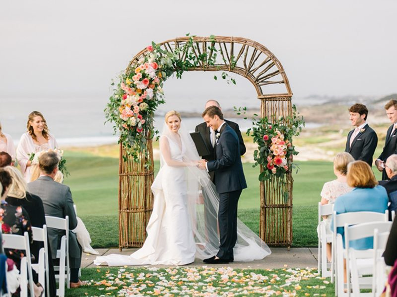Bride and groom with ceremony arch at Spanish Bay
