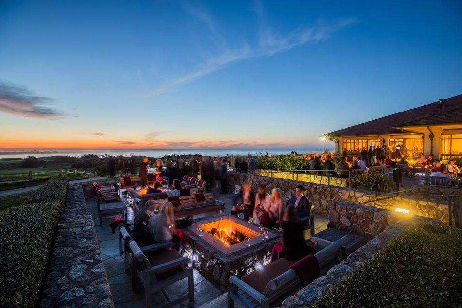 guests gathered around the spanish bay fire pits at dusk