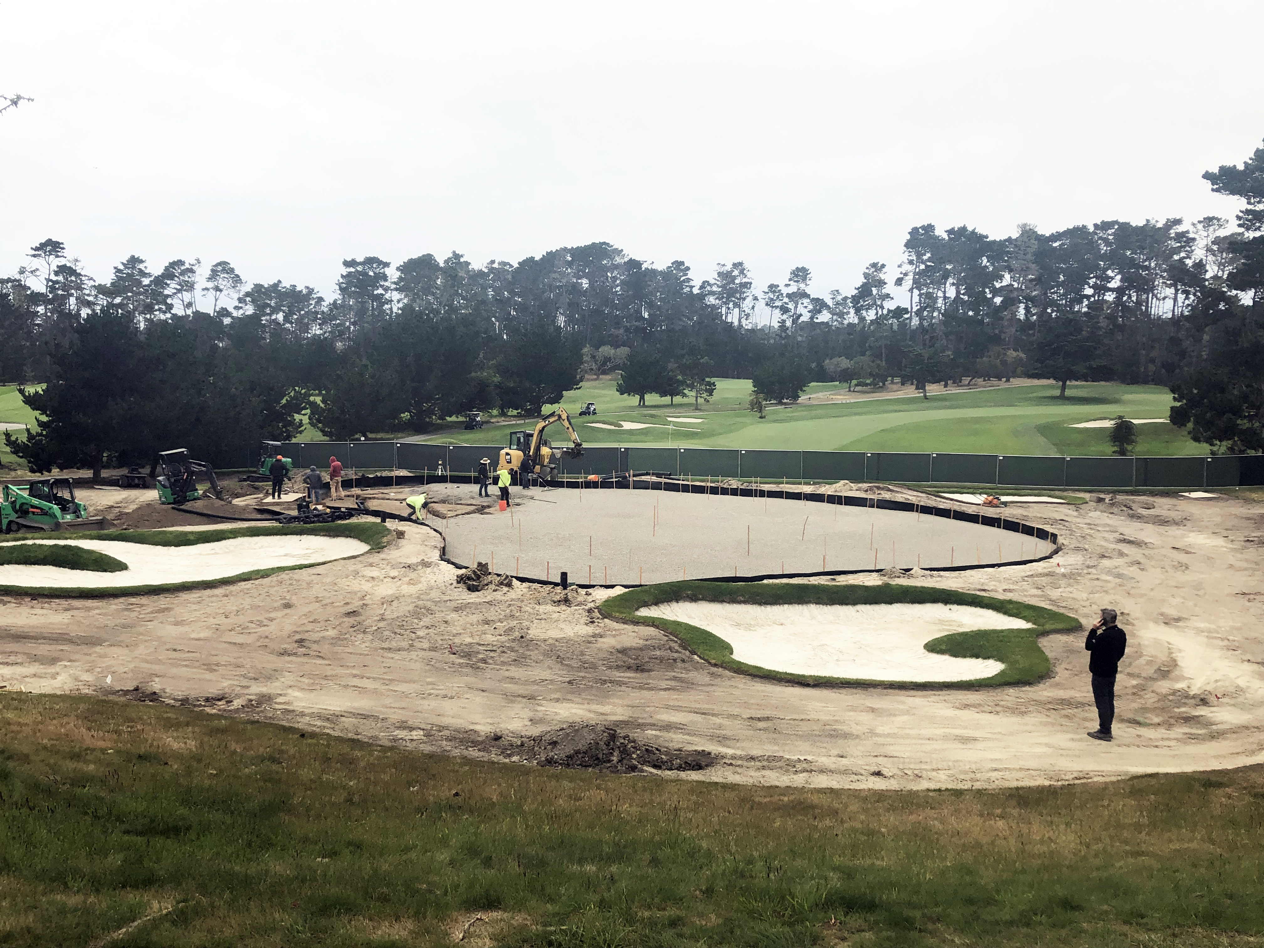 Renovation crew lays down a layer of gravel during spyglass hill 17th green renovation on a foggy day