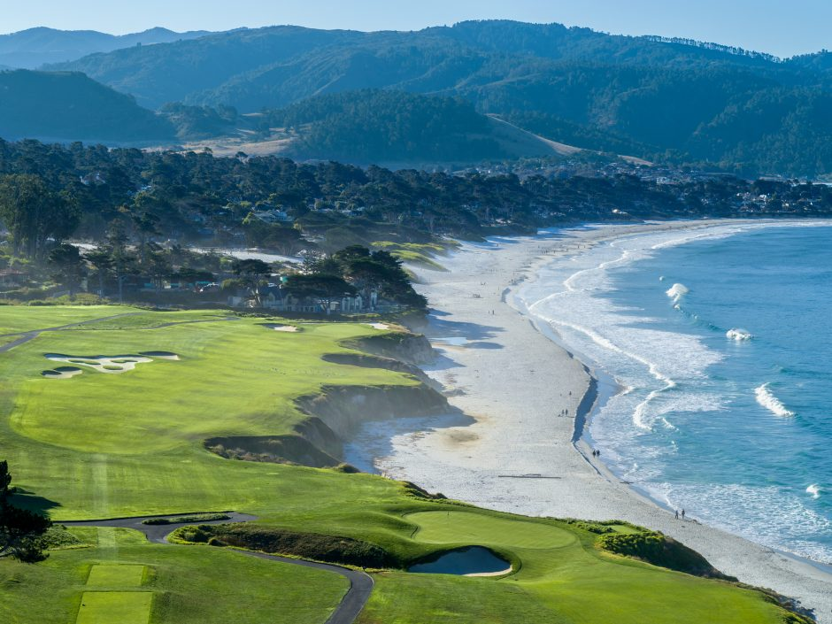 Aerial view of pebble beach golf links ninth and tenth holes with carmel beach and mountains in the background