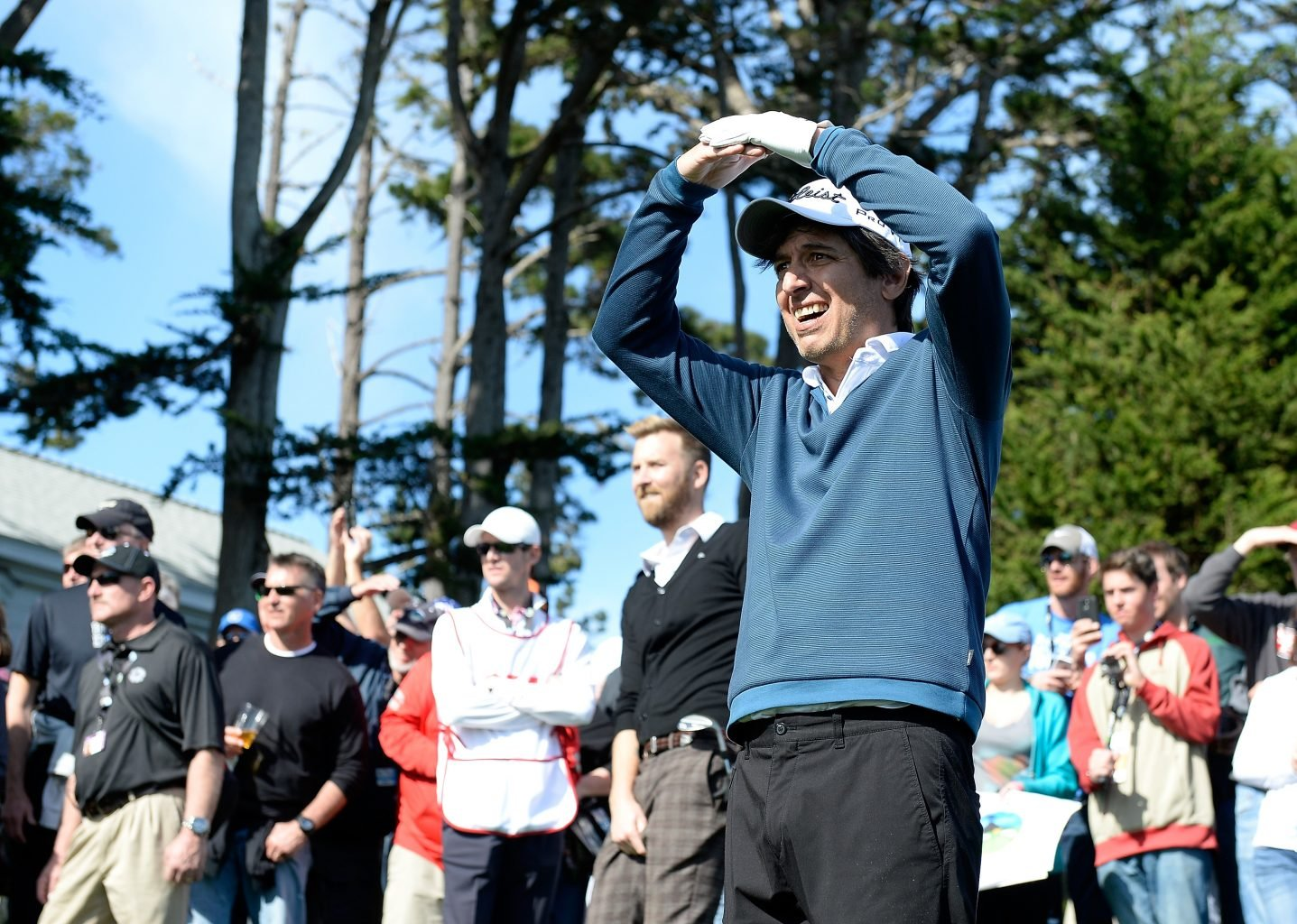 Actor Ray Romano standing with a crowd on a golf course