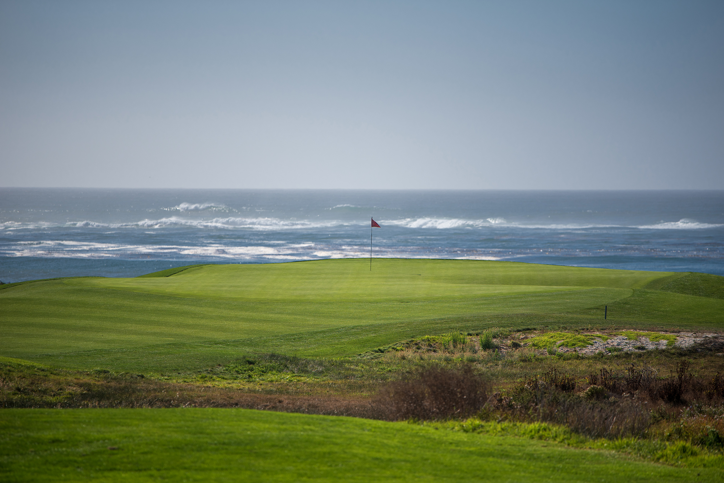 The first green at The Links at Spanish Bay from afar with the pacific ocean in the background