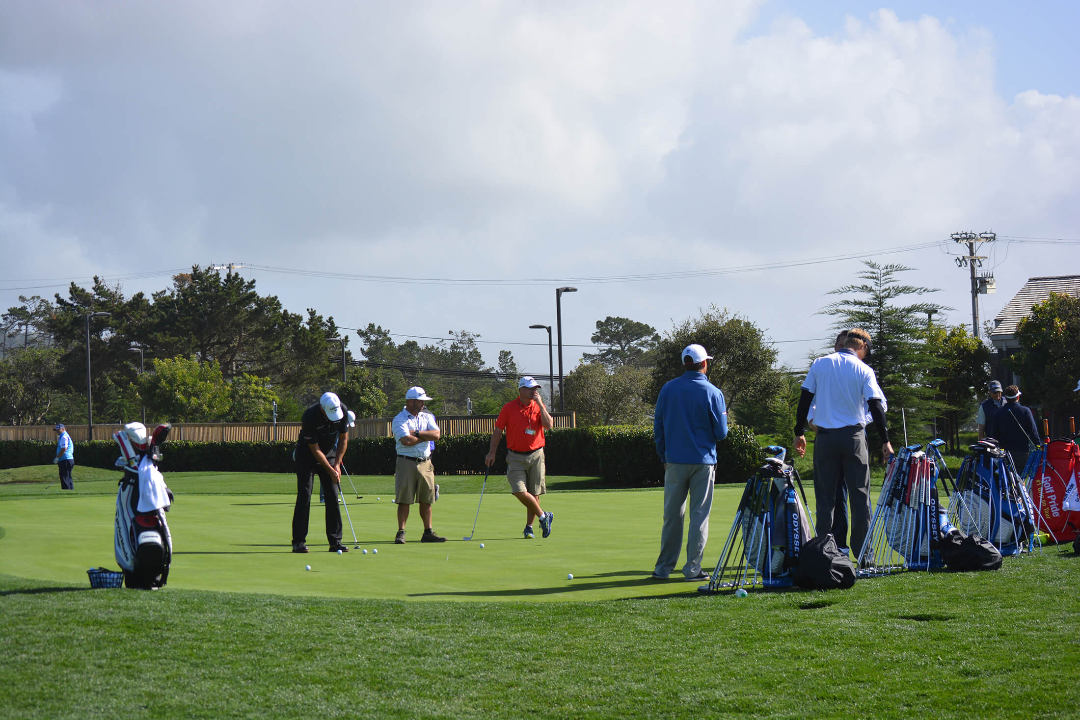 group of men stand around practicing their short game