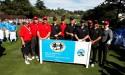 Golfers standing around banner