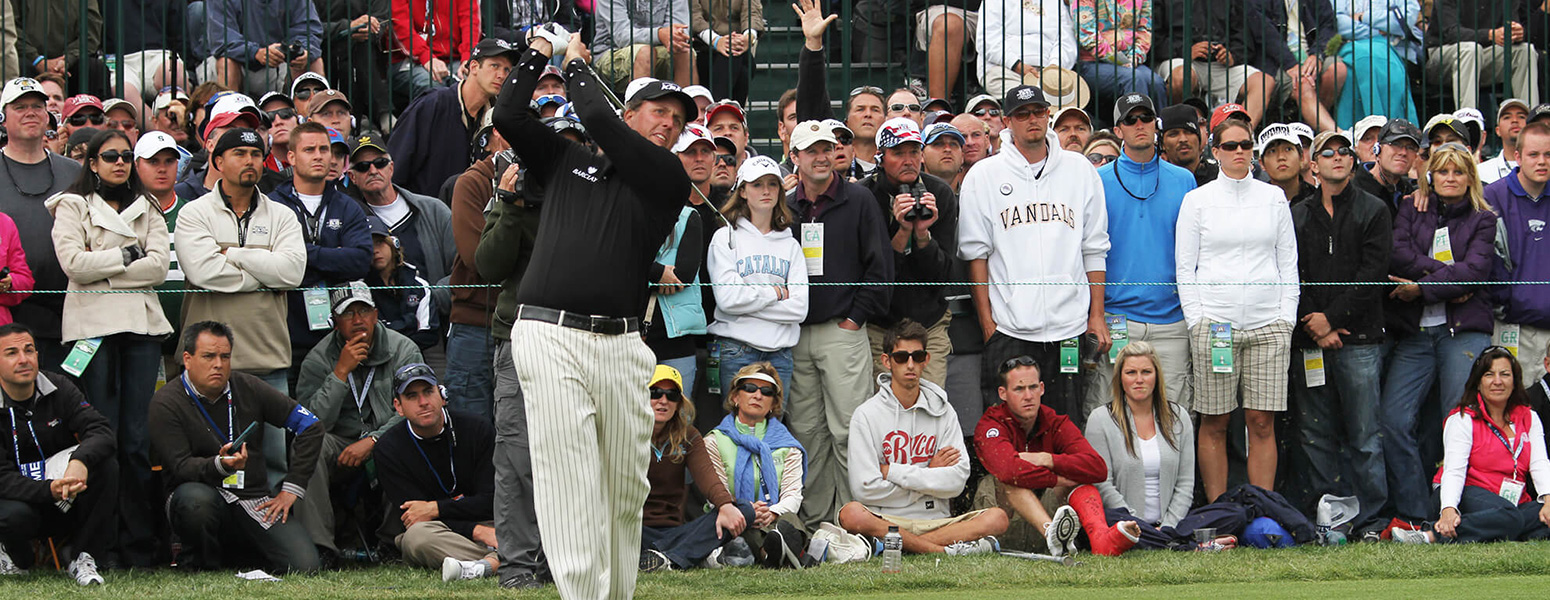 Man taking golf swing while crowd watches