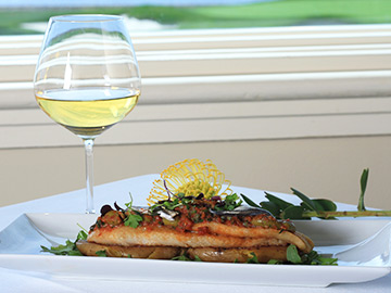 Salmon dish and glass of wine