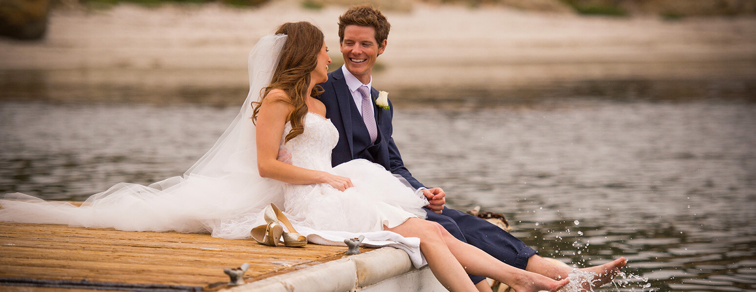 Bride and a groom sitting on a dock with their feet in the water.