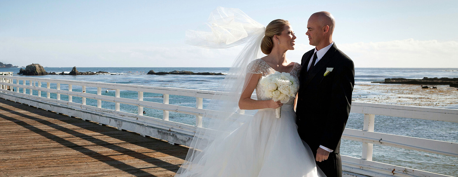 Bride and groom standing in front of the ocean